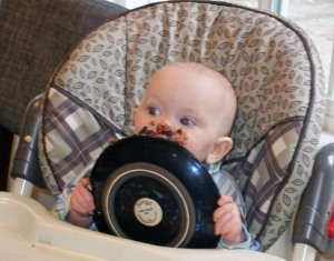 The one-year-old gripped both sides of the plate and hoisted his birthday cake to his face like pie to a circus clown.